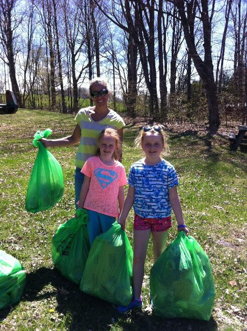 Three Green Up participants show off their trash haul.